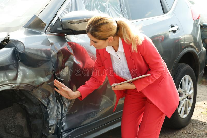 Agente de seguros com a tabuleta que inspeciona carro quebrado imagem de stock