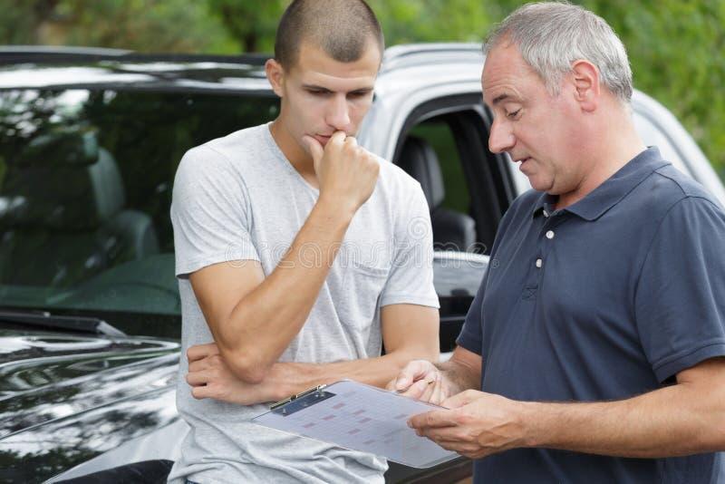 Agente de seguros Inspecting Damaged Car do ajustador de perda imagens de stock royalty free
