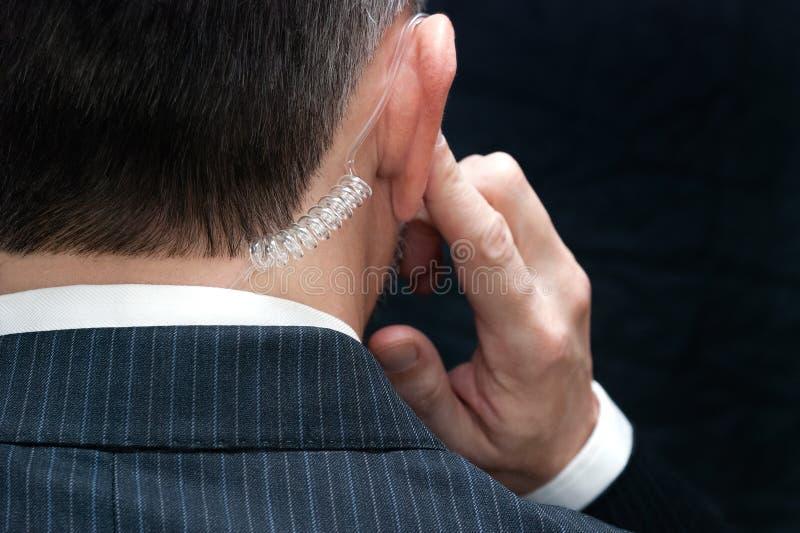 Agente de serviço secreto Listens To Earpiece, atrás fotografia de stock
