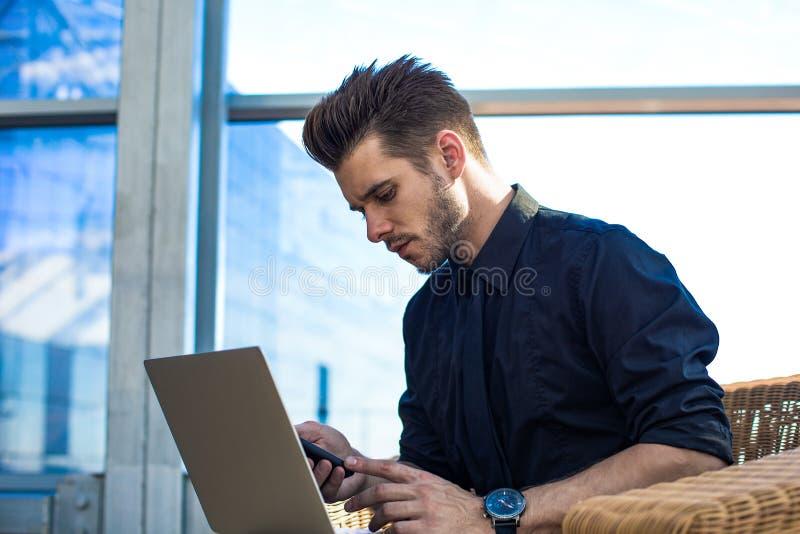 Agente de sexo masculino que comprueba el email en el teléfono móvil, después de usar el cuaderno imagen de archivo