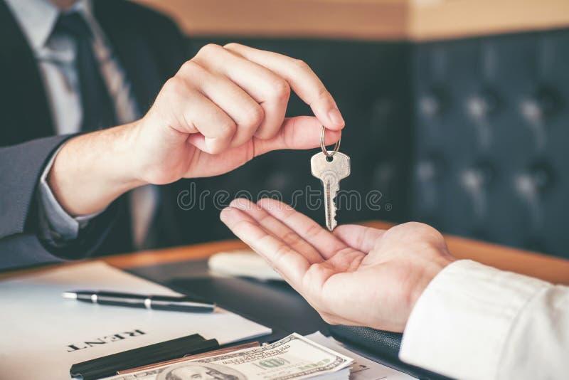 Agente de venta que da la casa dominante al contr del acuerdo del cliente y de la muestra fotografía de archivo