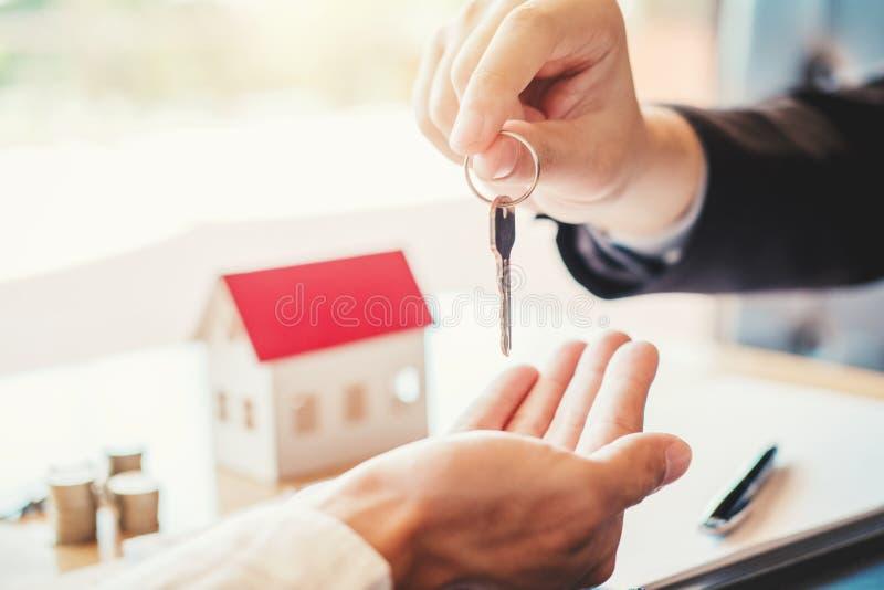 Agente de venta que da la casa dominante al contrato del acuerdo del cliente y de la muestra, concepto del hogar del seguro imagen de archivo libre de regalías