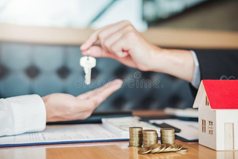 Agente de venta que da la casa dominante al contrato del acuerdo del cliente y de la muestra, concepto del hogar del seguro imagenes de archivo