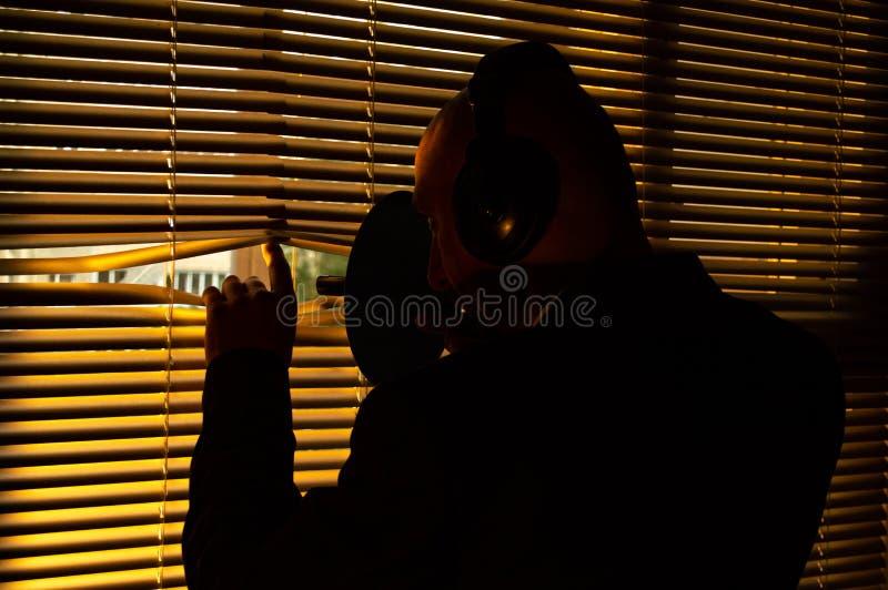 Agente del FBI que escucha detras de las puertas en un micrófono direccional fotografía de archivo