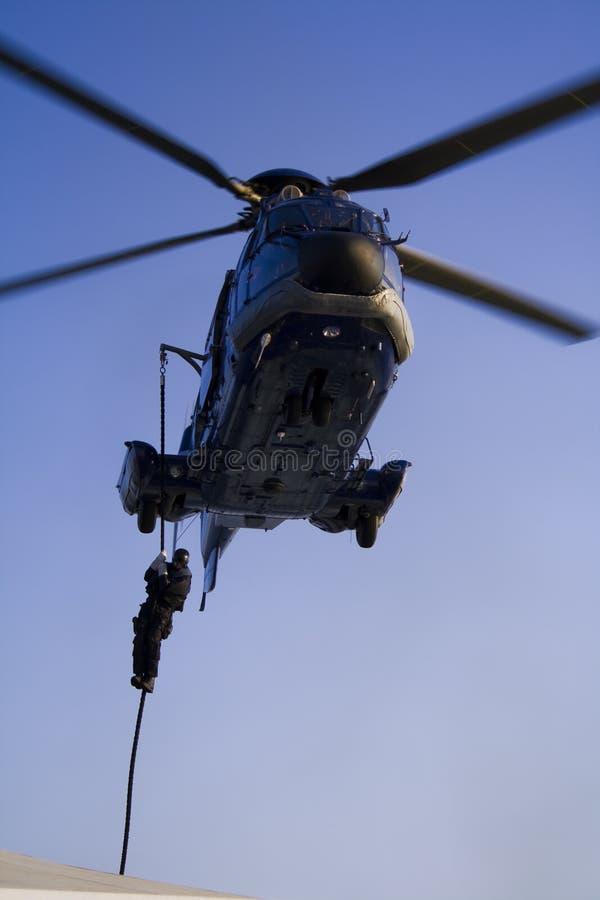 Agente del GOLPE VIOLENTO de GSG 9 que desciende en cuerda de un helicóptero foto de archivo libre de regalías