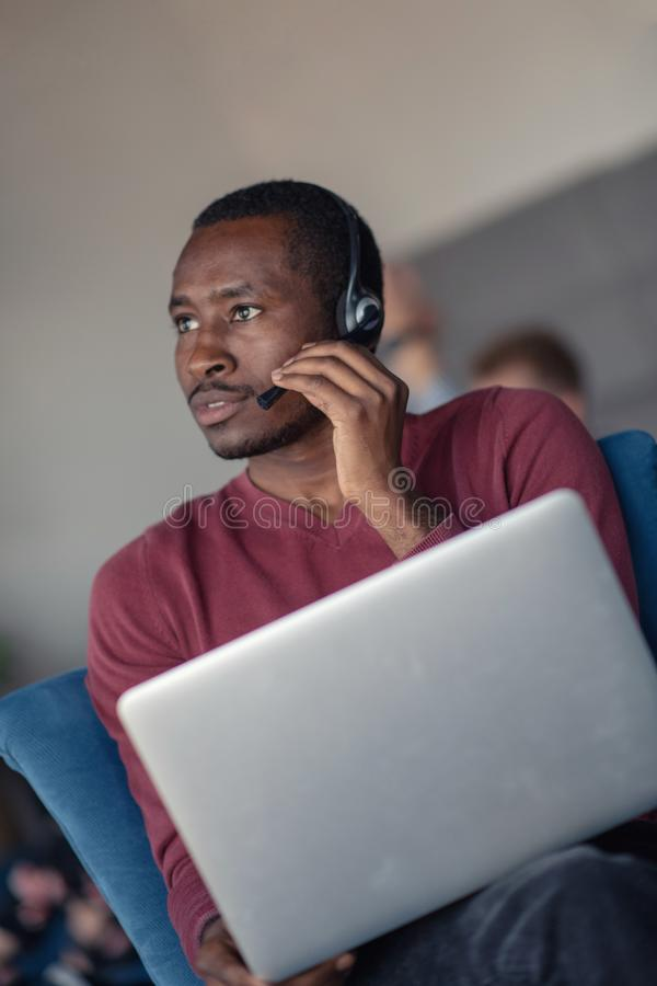 Agente di servizio di assistenza al cliente in un ufficio startup con il computer portatile immagini stock libere da diritti