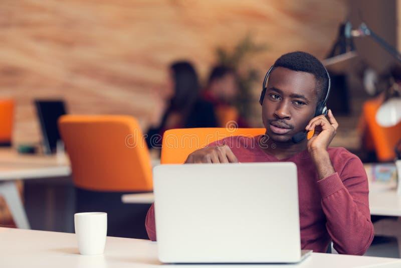 Agente di servizio di assistenza al cliente in un ufficio startup con il computer portatile immagini stock