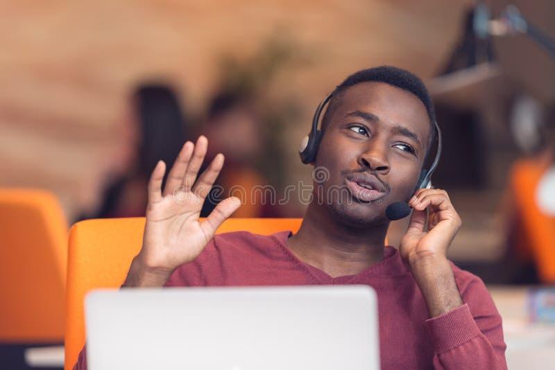 Agente di servizio di assistenza al cliente in un ufficio startup con il computer portatile fotografia stock