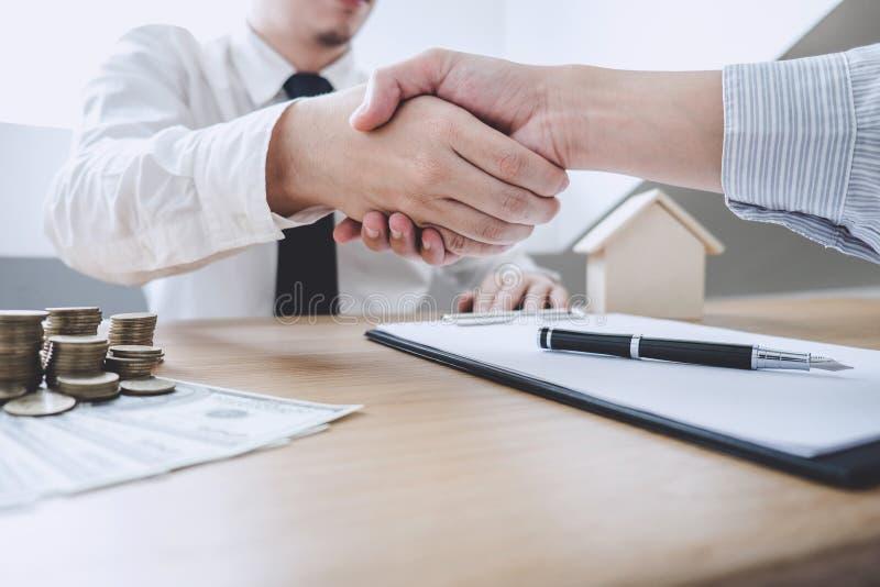 Agente e cliente dell'agente immobiliare che stringono le mani dopo la firma dei capitolati d'oneri per l'acquisto della realtà d fotografie stock libere da diritti