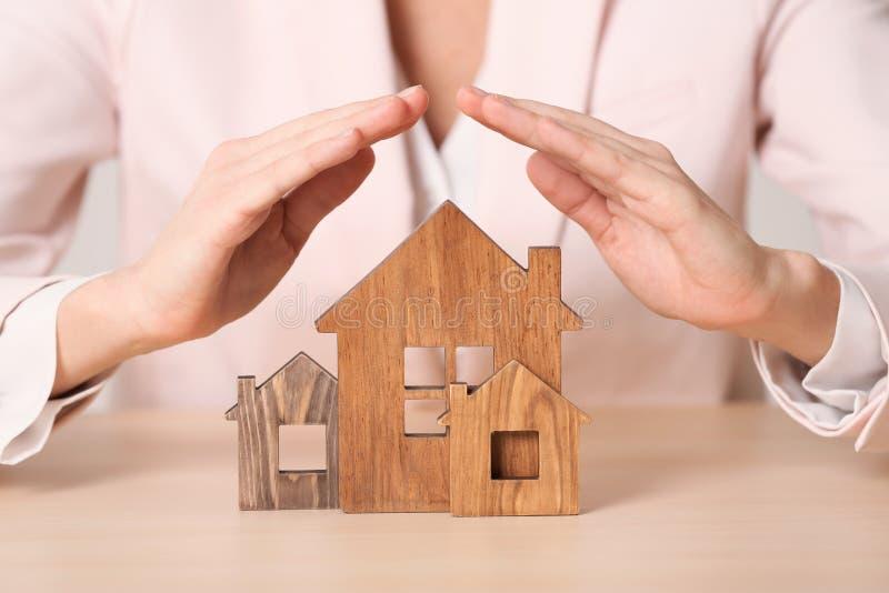 Agente fêmea que cobre casas de madeira na tabela Dirija o seguro fotografia de stock royalty free