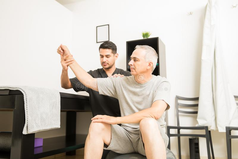 Agente físico Examining Hand Movements del paciente en clínica foto de archivo libre de regalías
