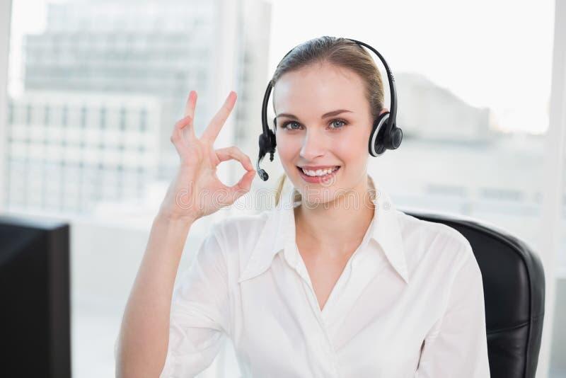 Agente felice di call-center che esamina macchina fotografica che dà segno giusto fotografie stock