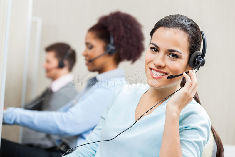 Agente femenino sonriente In Office del servicio de atención al cliente fotografía de archivo