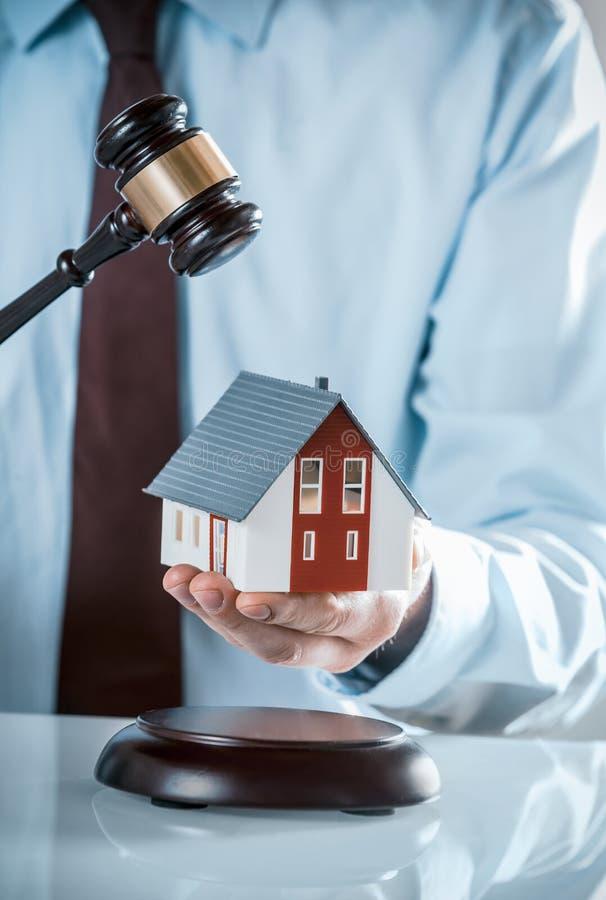 Agente Holding Miniature House com martelo de madeira foto de stock
