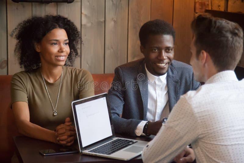 Agente immobiliare caucasico che consulta i clienti neri alla riunione del caffè fotografia stock libera da diritti