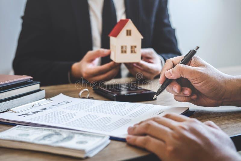 Agente immobiliare che fornisce casa e le chiavi al cliente dopo la firma del bene immobile del contratto di accordo con la forma immagini stock
