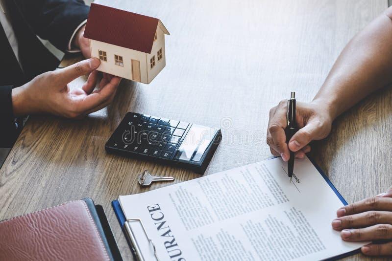 Agente immobiliare che fornisce casa e le chiavi al cliente dopo la firma del bene immobile del contratto di accordo con la forma immagini stock libere da diritti