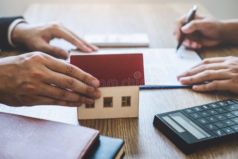 Agente immobiliare che fornisce casa e le chiavi al cliente dopo la firma del bene immobile del contratto di accordo con la forma fotografia stock