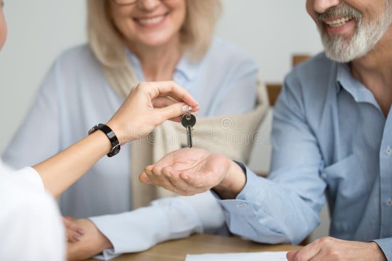 Agente immobiliare che fornisce chiave senior delle coppie alla nuova casa alla riunione immagine stock libera da diritti