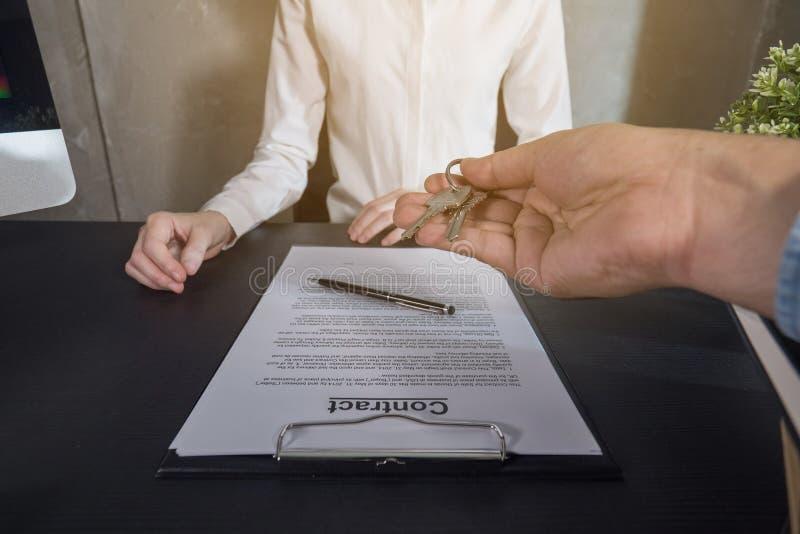 Agente immobiliare che fornisce le chiavi alla femmina che affitta o che compra appena nuova casa fotografia stock libera da diritti