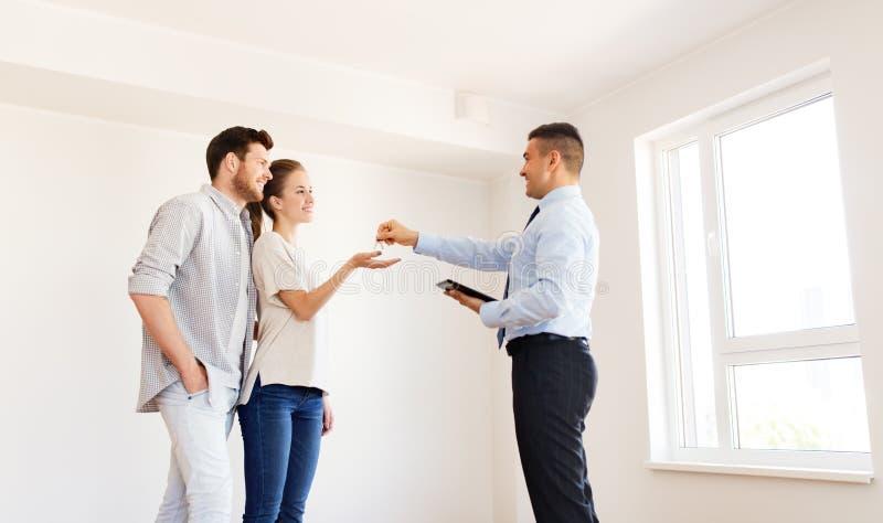 Agente immobiliare che fornisce le chiavi dalla nuova casa alle coppie felici immagini stock libere da diritti
