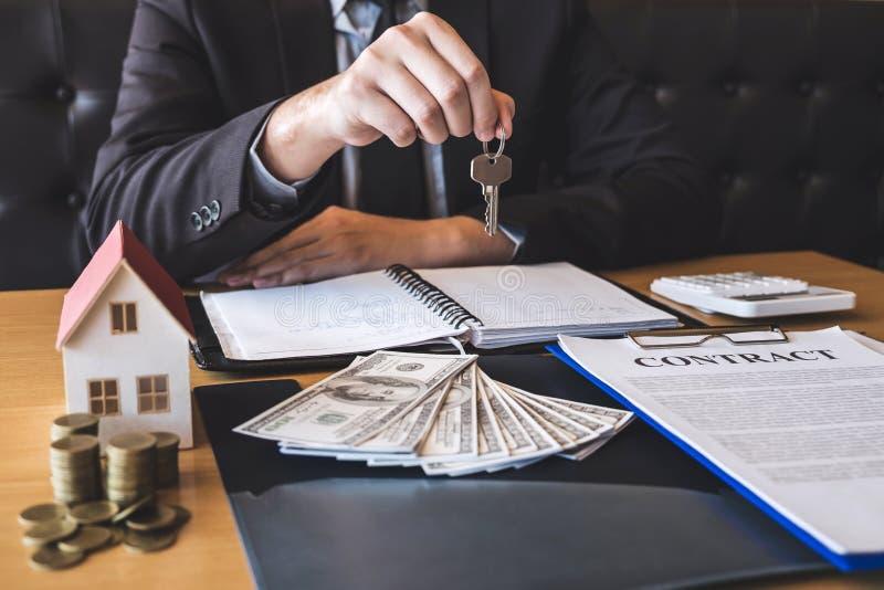 Agente immobiliare che fornisce le chiavi della casa al cliente dopo la firma del bene immobile del contratto di accordo con la f fotografia stock libera da diritti