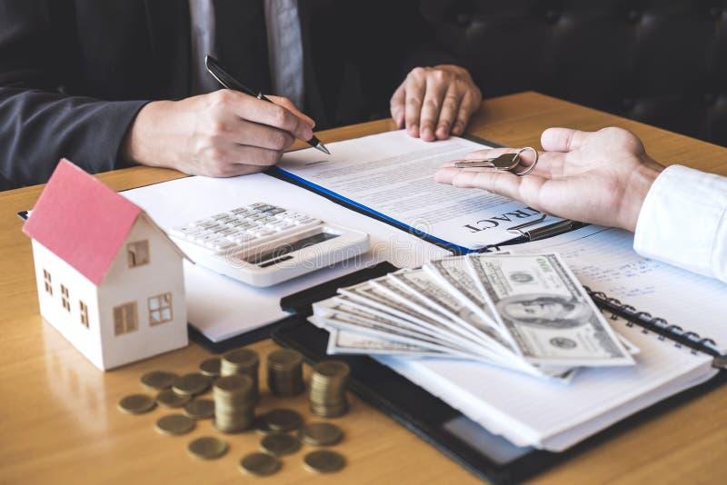 Agente immobiliare che fornisce le chiavi della casa al cliente dopo la firma del bene immobile del contratto di accordo con la f immagini stock