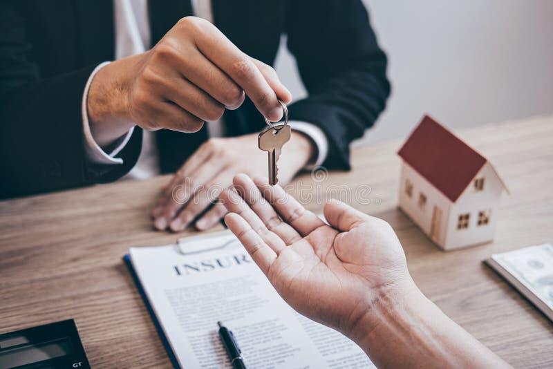 Agente immobiliare che fornisce le chiavi della casa al cliente dopo la firma del bene immobile del contratto di accordo con la f immagine stock