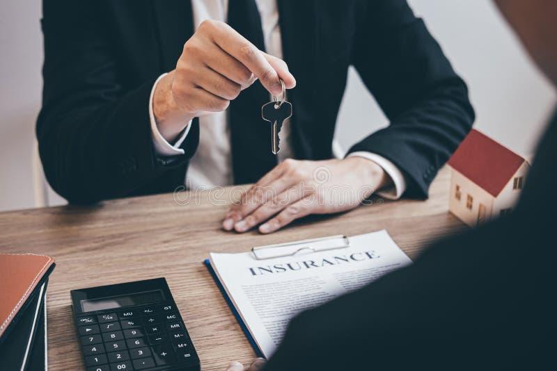 Agente immobiliare che fornisce le chiavi della casa al cliente dopo la firma del bene immobile del contratto di accordo con la f immagine stock libera da diritti