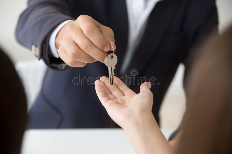 Agente immobiliare che fornisce le chiavi della donna alla nuova casa, fine sulla vista fotografia stock
