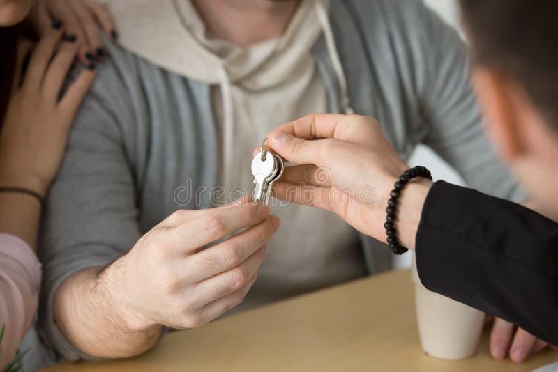 Agente immobiliare che fornisce le chiavi delle coppie, concetto d'acquisto della casa nuova, fine su immagini stock