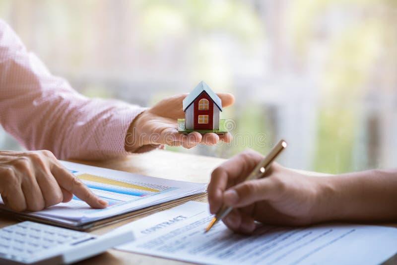 Agente immobiliare che indica dito sul documento che mostra costo complessivo che firma un documento cartaceo per la casa d'acqui immagini stock libere da diritti