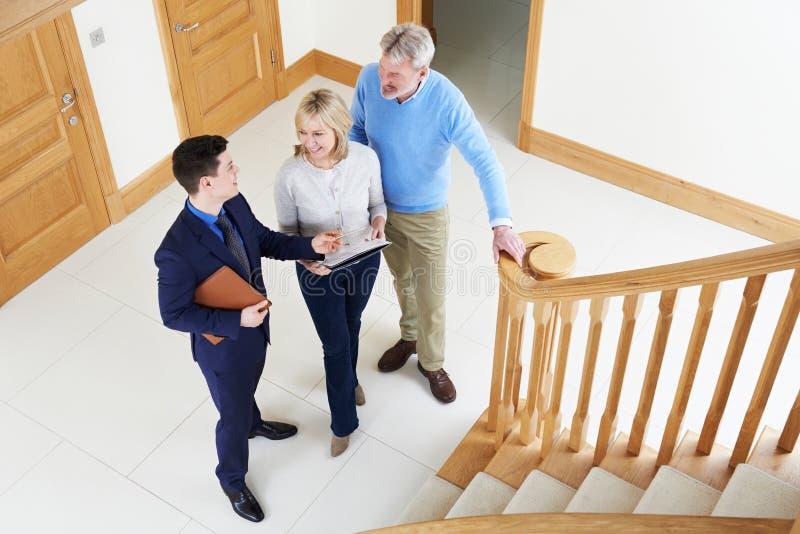Agente immobiliare che mostra le coppie mature intorno alla Camera da vendere fotografia stock