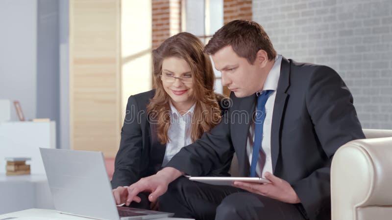 Agente immobiliare che mostra le foto sul computer portatile, convincente cliente comprare proprietà fotografie stock libere da diritti