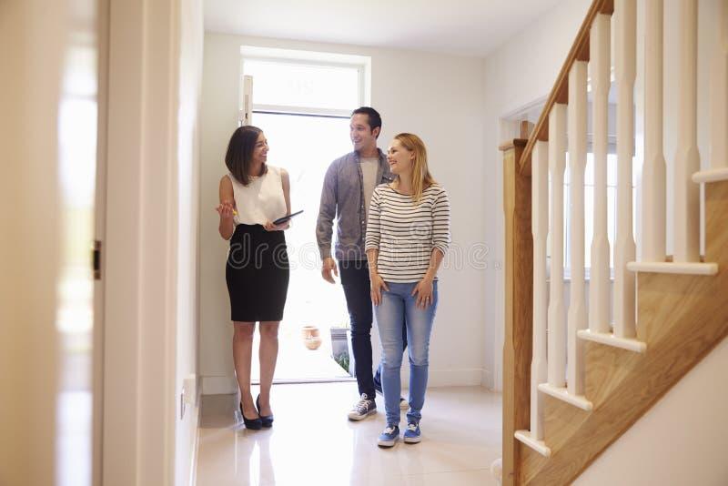 Agente immobiliare che mostra le giovani coppie intorno alla proprietà da vendere fotografia stock