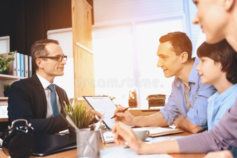 Agente immobiliare che si siede allo scrittorio in ufficio Il padre sta firmando il documento per il nuovo appartamento immagini stock