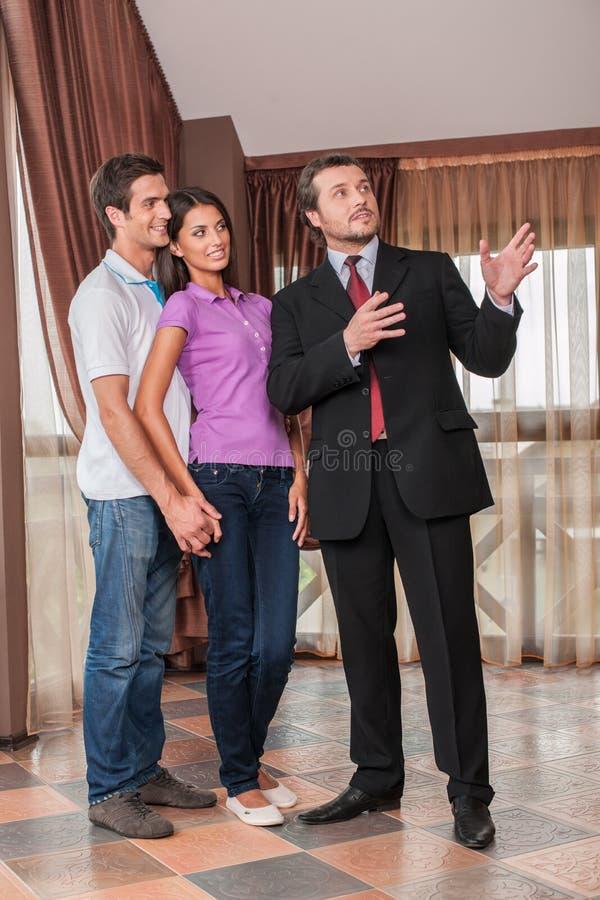 Agente immobiliare dell'uomo che mostra abbracciando le coppie nuova casa fotografie stock libere da diritti