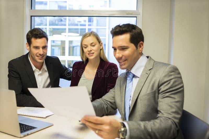 Agente immobiliare di riunione delle coppie per comprare proprietà immagini stock libere da diritti
