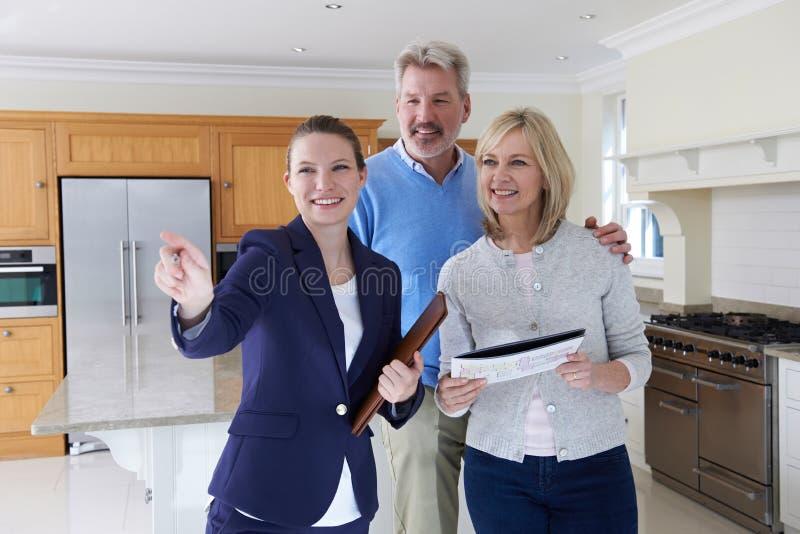 Agente immobiliare femminile che mostra le coppie mature intorno alla Camera fotografie stock libere da diritti