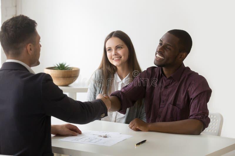 Agente immobiliare interrazziale soddisfatto felice di handshake delle coppie che fa con riferimento a immagine stock libera da diritti