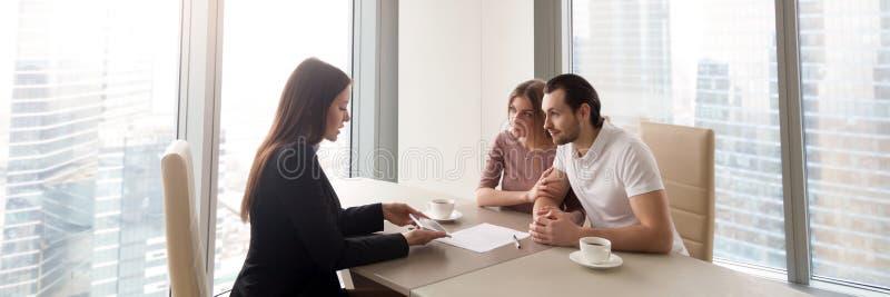 Agente immobiliare orizzontale di immagine e giovani coppie che discutono nuova pianta della casa immagini stock libere da diritti