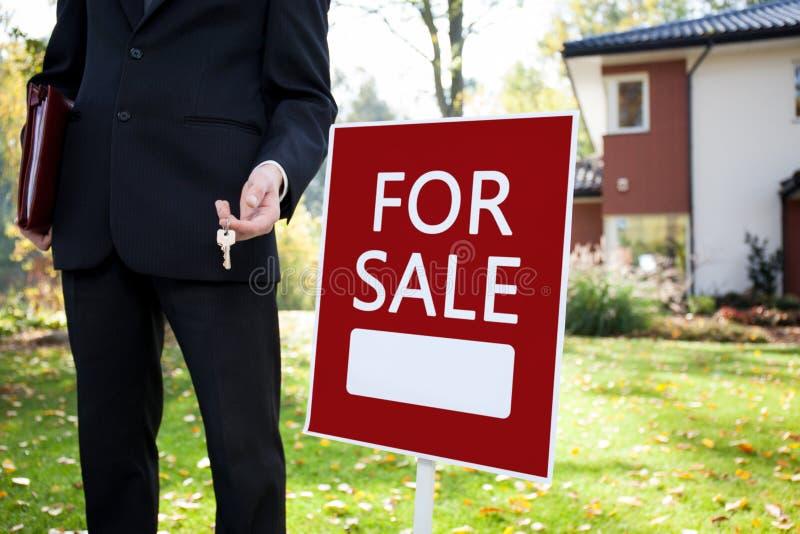 Agente imobiliário com chaves e sinal fotos de stock