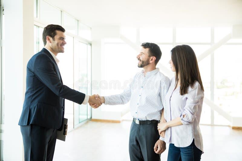 Agente imobiliário Congratulating To Couple para comprar a casa nova foto de stock