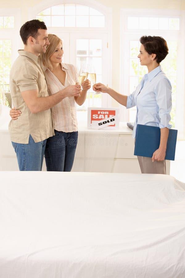 Agente imobiliário e pares que comemoram fotos de stock royalty free