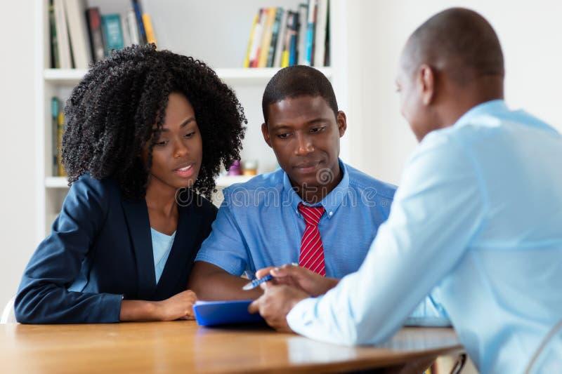 Agente imobiliário falando sobre uma nova casa com um casal africano imagens de stock royalty free