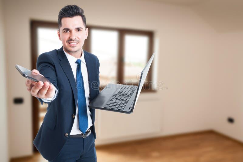 Agente imobiliário ocupado com portátil e smartphone foto de stock royalty free