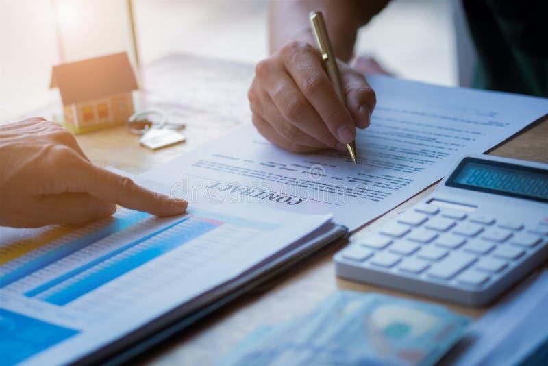 Agente imobiliário que aponta o dedo no documento que mostra o custo total que assina um documento de papel para a casa de compra fotografia de stock