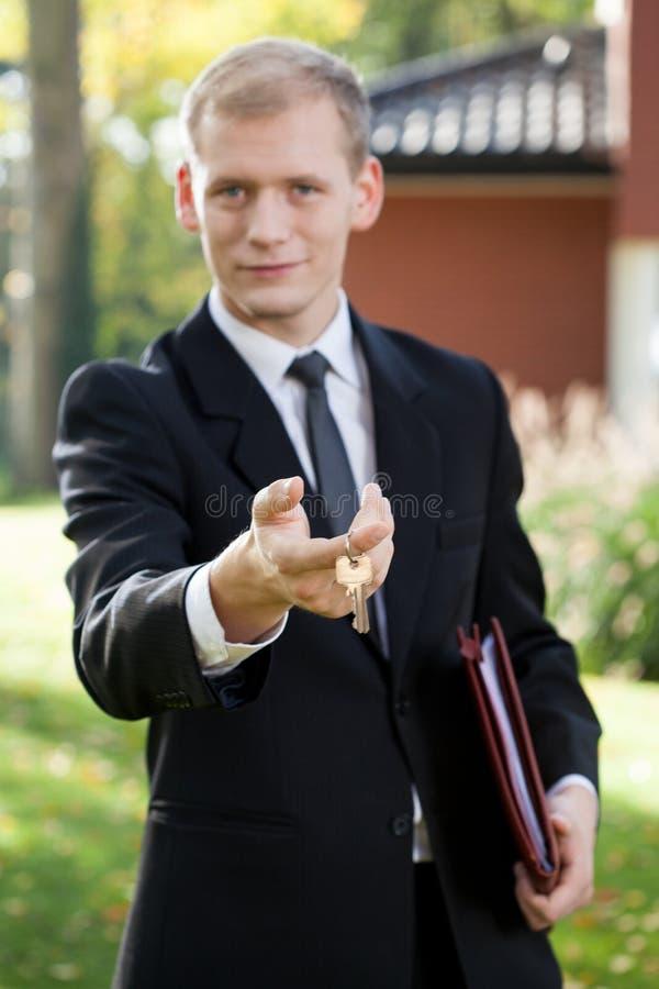 Agente imobiliário que guarda chaves imagens de stock