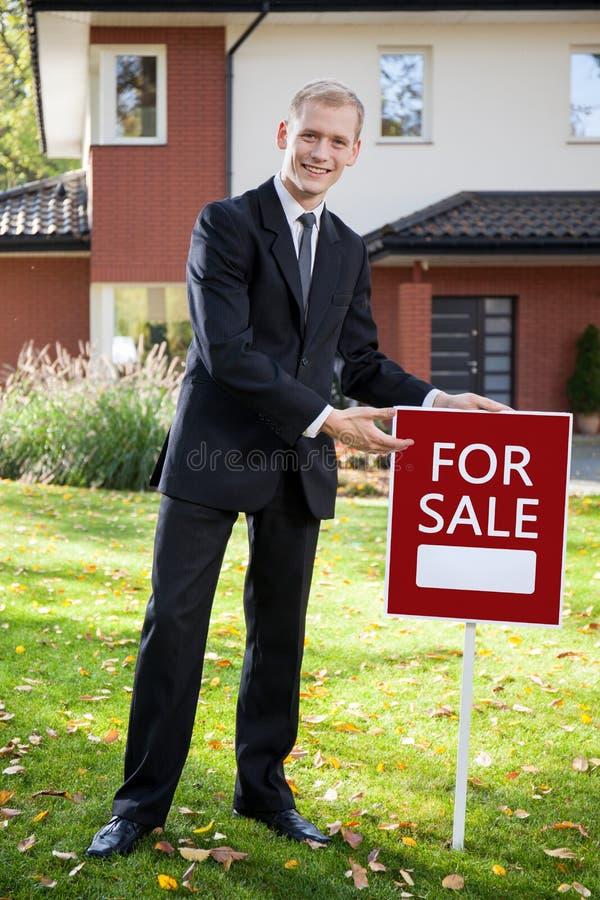 Agente imobiliário que guarda o sinal fora fotografia de stock