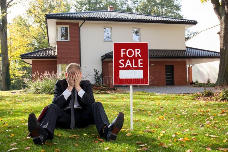 Agente imobiliário que senta-se fora da casa fotografia de stock